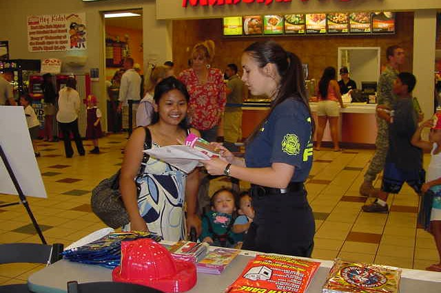 SCHOFIELD BARRACKS, Hawaii - Angela Sanders, an inspector with the Federal Fire Department (FFD), shares fire safety tips with family members at the Baskin-Robbins 31 cent a Scoop Night at the Post Exchange Mall Food Court, April 29.