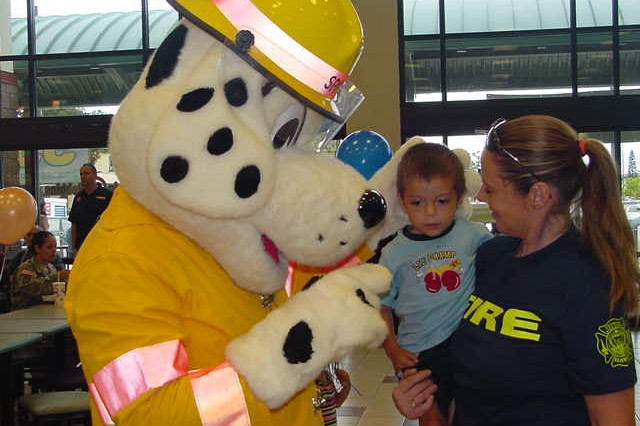 SCHOFIELD BARRACKS, Hawaii - Sparky the Fire Dog and Shannon Gipaya, an inspector with the Federal Fire Department, visit with children and their families at the Baskin-Robbins 31 cent a Scoop Night at the Post Exchange Mall Food Court, April 29.