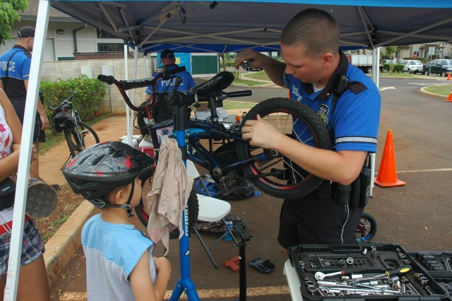 SCHOFIELD BARRACKS, Hawaii - Spc. Luke Schmidt, 13th Military Police Battalion, (right) checks the bike belonging to 6-year-old Wugun Connor, May 2, at the bike rodeo, at the Porter Community Center. Military Police were on hand throughout the day to check all gear for safety and offer advice on proper riding techniques.