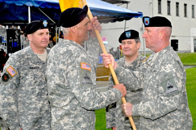 Command Sgt. Maj. Roger Blackwood (right) hands the 1st Armored Division colors to Maj. Gen. Mark P. Hertling who in turn will pass them to Lt. Gen. Kenneth W. Hunzeker (left), V Corps commander, and then to incoming division commander, Maj. Gen. Terry A. Wolff, to mark the ceremonial passing of the 1st Armored Division's leadership.