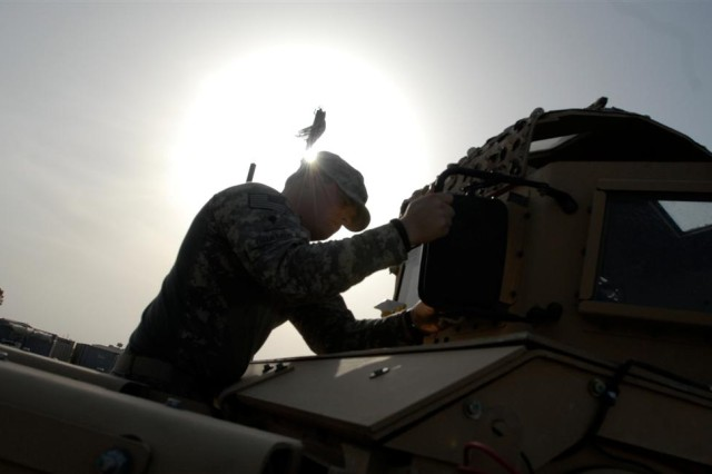 Spc. Thomas Bramble, a broadcast journalist, helps crewmembers clean the mirrors and windows of an up-armored humvee, Joint Base Balad, Iraq April 14. The humvee was part of a convoy which escorted fuel trucks down to Convoy Support Center Scania, south of Baghdad.