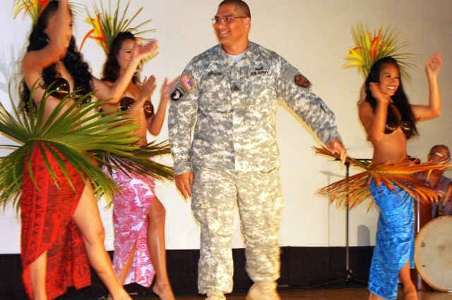 Staff Sgt. Kaimi Kawai, an information management specialist, 24th Detachment, 1101st U.S. Army Hawaii Garrison Support Unit, attempts to perform a hula dance with dancers from the Dizanne Productions dance company during an Asian-Pacific American Heritage month celebration.