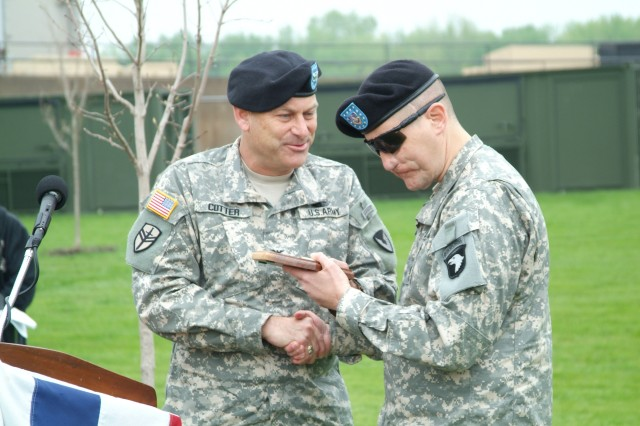 Rock Island Arsenal Joint Manufacturing and Technology Center Commander, Col. Craig S. Cotter, shares a token of appreciation with Master Sgt. Jeffrey Mittman at the FRAG Kit 6 roll out ceremony at Rock Island Arsenal Joint Manufacturing and Technology Center.
