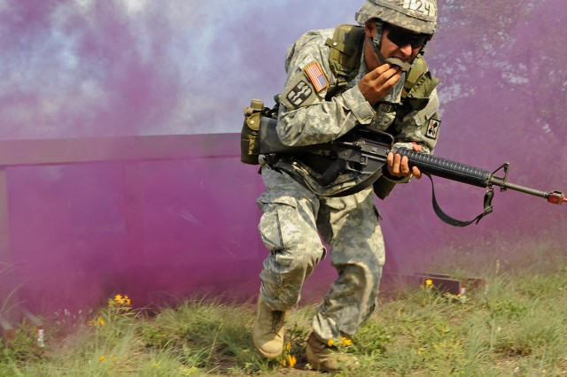 Sgt. 1st Class Ricardo Gutierrez moves forward through a haze-filled obstacle course during a two-week test to earn the prestigious Expert Field Medical Badge at Camp Bullis, Texas. Guitierrez is assigned to the 264th Medical Battalion at nearby Fort Sam Houston.