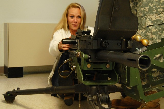 """A No Slack"""" Soldier's wife tries her hand at one of the weapons systems presented on GI Jane Day at Fort Campbell, KY, May 1, 2009. GI Jane Day helps """"No Slack"""" wives get a better understanding of a Soldiers job."""