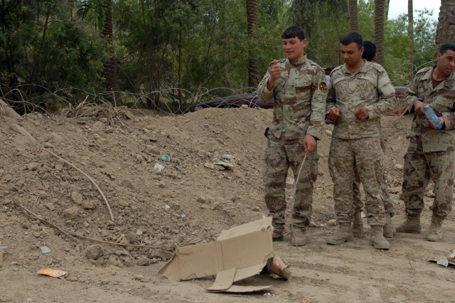 "BAGHDAD - Iraqi Soldiers from the 11th Iraqi Army Division Headquarters in Rusafa approach a suspecte improvised explosive device, while on an IED identification lane during training with the ""Dark Knight"" Soldiers from Headquarters and Headquarters Company, 1st Brigade Special Troops Battalion, 1st Brigade Combat Team, 1st Cavalry Division in Rusafa May 10."