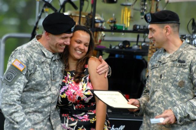 Combined Arms Center and Fort Leavenworth Commander Lt. Gen. William Caldwell IV hugs Marquita Jones as CAC Command Sgt. Philip Johndrow presents her a certificate of appreciation and commemorative pin during a ceremony honoring military spouses for Military Spouse Appreciation Day May 8 at Merritt Lake.