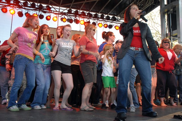 "As vocalist Gina Gonzalez belts out ""Lady Marmalade,"" Fort Leavenworth women and girls invited on stage dance and sing along during the Lt. Dan Band concert May 8 at Merritt Lake."
