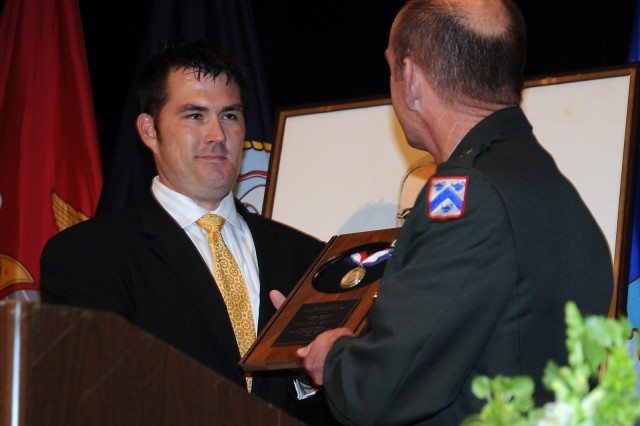 Former Navy SEAL Marcus Luttrell receives the Philip Pistilli Silver Veteran's Medal from Brig. Gen. Edward C. Cardon during the Harry S. Truman Good Neighbor Award Foundation luncheon May 7 in Kansas City Mo.
