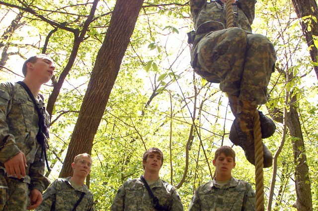Junction City (Kan.) Junior ROTC cadets race to complete the rope climb, each team member climbing the rope to ring a bell before moving on the the next challenge within the cross-country litter carry event May 9 at Camp Miles, Fort Leavenworth, Kan.