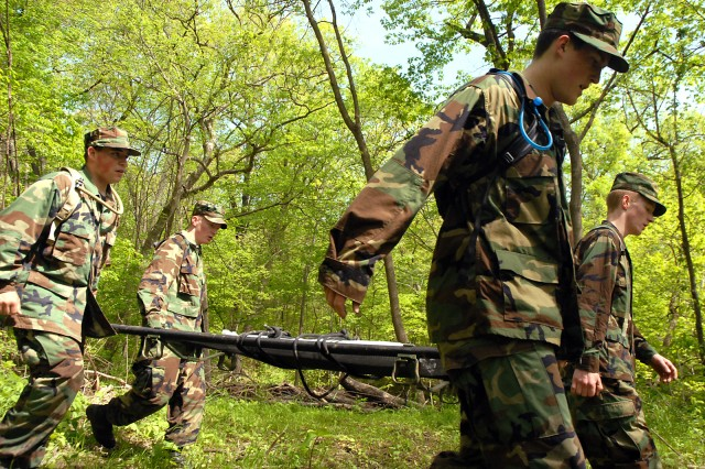 Cadet Ensign Zach Stultz, Cadet Commander James Kenny, Cadet Commander Andrew Lake and Cadet Ensign Cody Stultz of Shawnee Mission West Navy Junior ROTC participate in the cross-country litter carry event during the Leavenworth High School-sponsored Raider Challenge May 9 at Camp Miles, Fort Leavenworth, Kan. Cadets applied first aid, climbed a rope, tied knots and pulled a humvee as a team during the litter carry. Other events included land navigation and blind tent set-up.