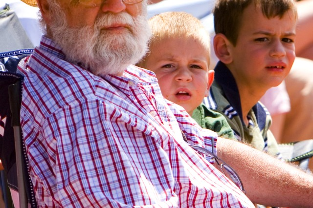 Veteran Jim Wilson shares his Family history with the 3rd ID with his grandsons.  Jake,  4 (left), and Allen, 8, watch as the long train of heavy armored vehicles pass by during the 2nd HBCT, 3rd ID's pass in review at Fort Stewart, May 8.