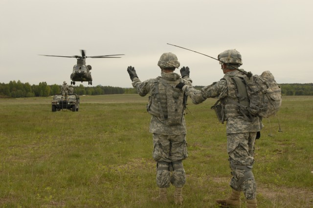 Soldiers from the 173rd Airborne Brigade Support Battalion guide a Chinook while Soldiers practice sling load operations in Grafenwoehr, Germany, on May 5, 2009.