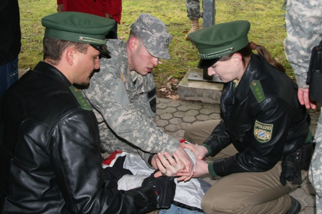 Spc. Aaron Smith, U.S. Army Garrison Ansbach, Germany, Military Police, along with German Polizei Andreas Doppelhammer, left, and Sabine Hofmann, prepare to handcuff a simulated suspect during a training exercise.