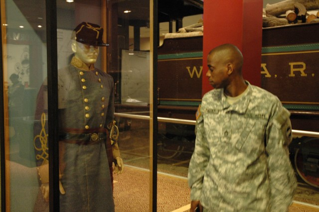 Sgt. 1st Class Tulloch, funeral team color guard NCOIC, appears to be inspecting the uniform on display at the Atlanta Cyclorama.