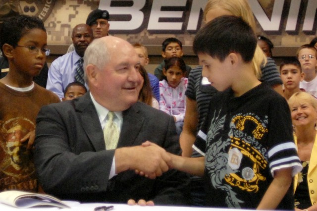 Gov. Sonny Perdue shakes hands with Marcus Morena, a fifth-grader at Dexter Elementary, May 7 at Freedom Hall after signing two bills to ease school transitions for military children.