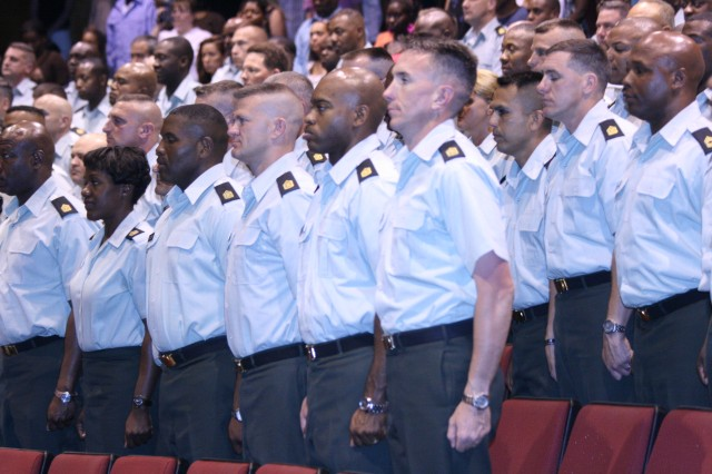 Members of U.S. Army Sergeants Major Academy Class 59 stand for the entrance of the official party during their Baccalaureate ceremony inside USASMAAca,!a,,cs East Auditorium, May 7.