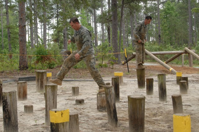 """Maj. Craig Gendreau (left), the executive officer for the 96th Civil Affairs Battalion (Airborne), and Command Sgt. Maj. Thomas Wall, the 95th CA Brigade command sergeant major, navigate the Island Hopper obstacle on the Darby Queen obstacle course during the 2009 Best Ranger Competition at Fort Benning, Ga., May 8."""""""