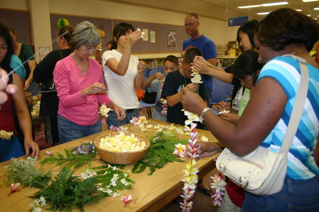 SCHOFIELD BARRACKS, Hawaii - Family members carefully thread plumeria flowers through a long needle and onto strings to make lei during a Hawaiian cultural demonstration, May 5, at Sgt. Yano Library. More than 60 participants learned the history, art and etiquette of lei making and giving during the two-hour presentation hosted by members of the Kapolei Hawaiian Civic Club. The event was the first in a series of Hawaiian cultural programs the library is offering with the garrison's Native Hawaiian liaison, Annelle Amaral. The next program will be a Hula demonstration, June 10, 5:30-7 p.m. Contact the library for more information at 808-655-8002.