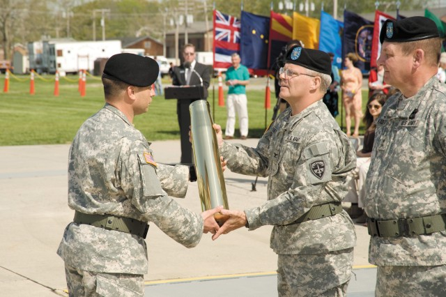 Col. John P. Rooney, center, former commander of the U.S. Army Aberdeen Test Center, accepts the ceremonial canister signifying the last round fired in his honor from Sgt. 1st Class Niko Troia during the ATC Change of Command ceremony April 28. Maj. Gen. Roger A. Nadeau, commanding general, U.S. Army Test and Evaluation Command, looks on.
