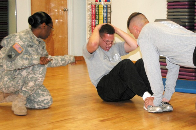 Sgt. Aaron Reyes, 38th EOD Detachment, Fort Stewart, Ga., knocks out a few sit-ups during the Army Physical Fitness Test given to all competitors. Staff Sgt. Tashika Prue, left, counts the repetitions while fellow competitor Spc. Elijah Sedig holds Reyes' feet.