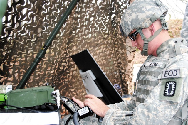 Spc. Elijah Sedig, 38th Explosives Ordnance Detachment, Fort Stewart, Ga., operates a radio during the Warrior Tasks portion of the 20th Support Command NCO and Soldier of the Year competition.