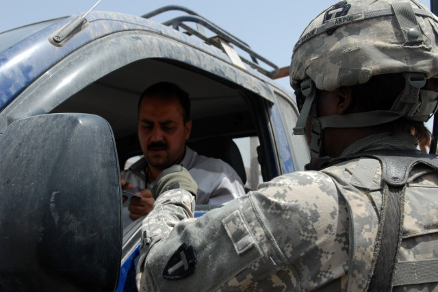 """BAGHDAD - Spc. Tiffany Frenchwood, a logistical specialist assigned to Apache Troop, 1st Squadron, 124th Cavalry Regiment, hands back a local national's ID at a checkpoint at Victory Base Complex here, May 14. Frenchwood is one of a handful of women who are assigned to the Texas National Guard cavalry unit here. """"We've been with these guys almost 10 months now and have gotten used to them,"""" said Frenchwood."""