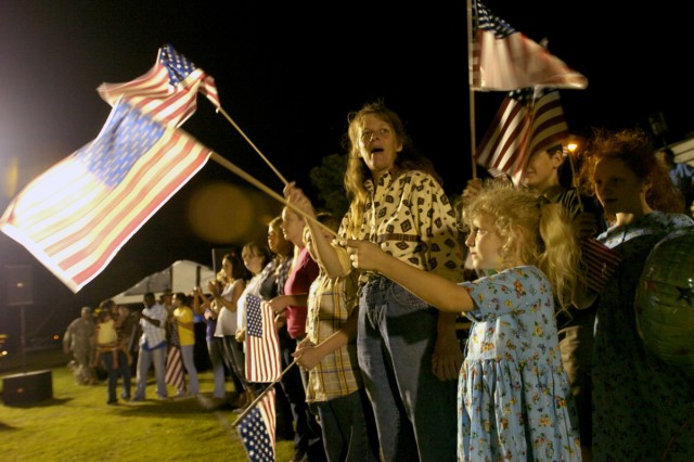 Becky Pemberton and her two daughters, Hannah, 6, and Breanne, 8, wait for the buses Pfc. Anthony Pemberton, 2nd Battalion, 7th Cavalry Regiment, 4th Brigade Combat Team, 1st Cavalry Division, and more than 200 other Soldiers came back on May 14, at a homecoming ceremony on Cooper Field in front of the division headquarters building after a year-long tour in Iraq.