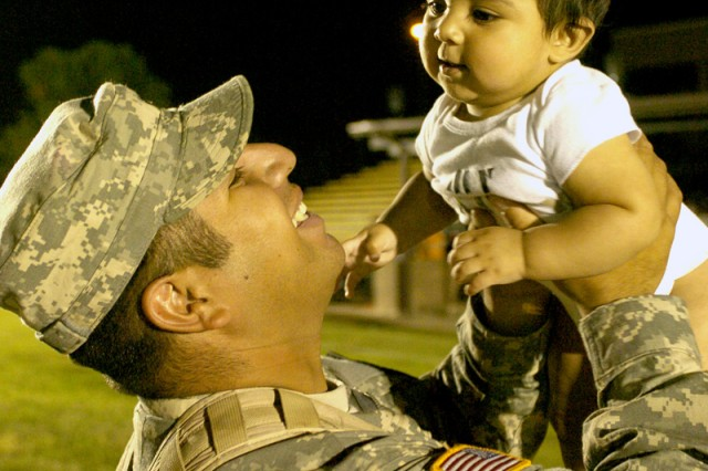 Spc. Miguel Meza, of Dinuba, Calif., lifts up his 7-month-old son, Angel, during a homecoming ceremony May 14, on Cooper Field, Fort Hood, Texas, as he and more than 200 other Soldiers from 4th Brigade Combat Team, 1st Cavalry Division, returned home after their year-long tour in Iraq.