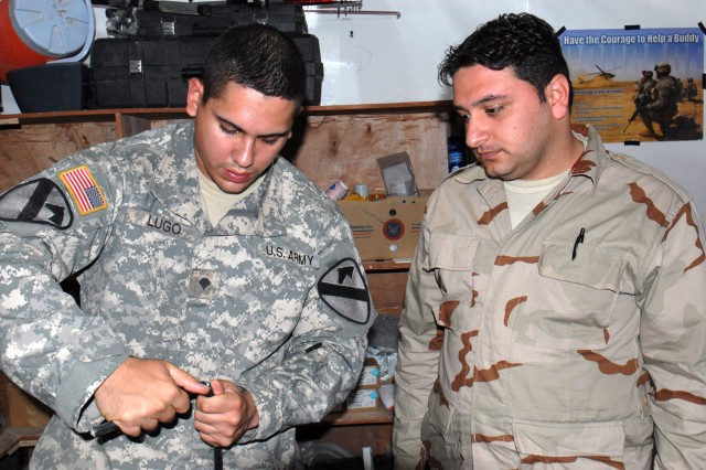 BAGHDAD - Spc. Jorge Lugo (left) assigned to Company C, Division Special Troops Battalion, 1st Cavalry Division, of San Juan, Puerto Rico, begins the process of cutting a fiber optic cable, May 13, so he can let Iraqi Army Sgt. 1st Class Saad Jafar Kareem demonstrate re-joining the delicate glass cables using a fusion splicer to melt the tiny glass fibers together. Fusion splicing creates a seamless joint in a fiber optic cable, which eliminates the need to install an entire new cable. Lugo said Kareem, who is a trained electrician, is a quick learner.