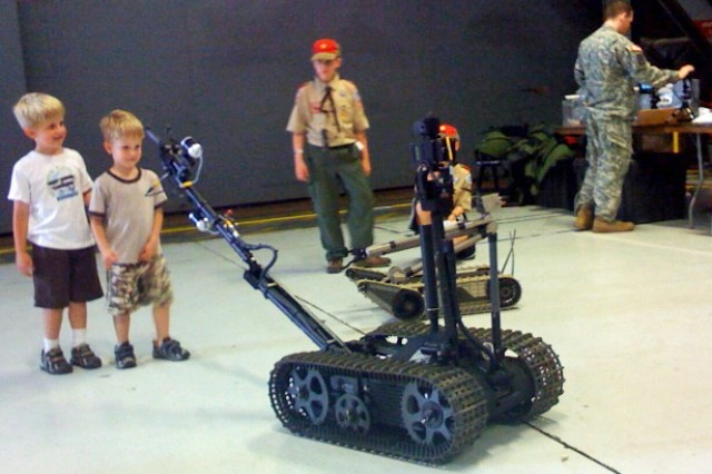 Children and Boy Scouts gather around PackBots operated by a Soldier from the 52nd Ordnance Group, Explosive Ordnance Disposal at the Joint Service Open House at Andrews Air Force Base, Md.