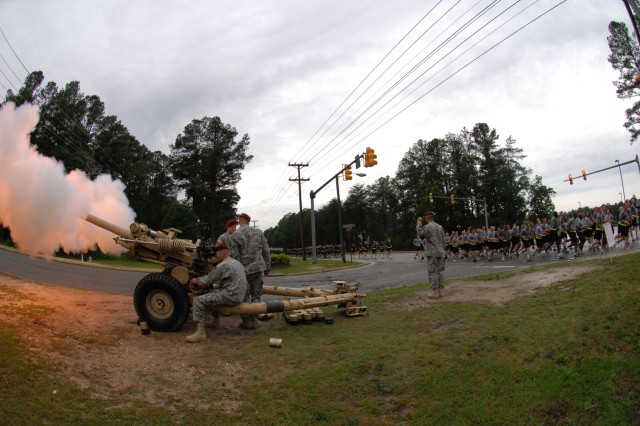 A Howitzer fires as thousands of Paratroopers from the 82nd Airborne Division run by during the four-mile division-wide run that kicked off the 82nd's All American Week celebration May 18. The annual event celebrating the 82nd's history and accomplishments is taking place from May 18-21 this year, despite the Division's multiple ongoing deployments overseas. (U.S. Army photo by Pfc. Victor J. Ayala, 49th Public Affairs Detachment)
