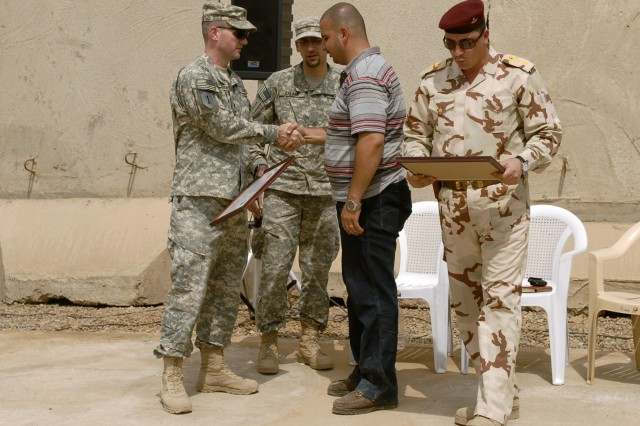 BAGHDAD - Lt. Col. John Richardson (left), commander, 5th Squadron, 4th Cavalry Regiment, 2nd Heavy Brigade Combat Team, 1st Infantry Division, Multi-National Division - Baghdad, and Lt. Col. Ali (right), commander, 2nd Battalion, 54th Brigade, 6th Iraqi Army Division, give framed certificates of appreciation to  Duraid Kassim Malik (center) during the closure ceremony of Joint Security Station Yarmouk in northwest Baghdad May 16. Malik allowed the Soldiers operating out of the JSS to live and work from his home and due to the improved security of the area, the JSS is no longer needed.
