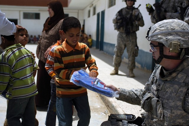 BAGHDAD-Hershey, Pa. native, Staff Sgt. Joseph Fimonetti, the fire support non-commissioned officer in charge, with 2nd Battalion, 112th Infantry Regiment, Multi National Division-Baghdad, hands out new book bags to Iraqi students at the Hamichun School May 15.