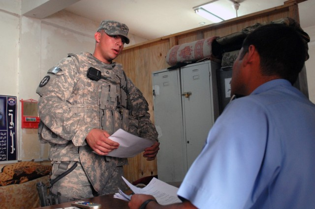 TAJI, Iraq - Pfc. Dustin Shuler, from Syracuse, N.Y., 591st Military Police Company, 93rd MP Battalion, 8th MP Brigade, checks numbers of detainees with Iraqi police at a station in Saab al-Bour, here, May 15. Soldiers of the 591st go over a number of areas with the Iraqi Police to make sure they are on the right track and offer assistance if they are not, said Shuler.