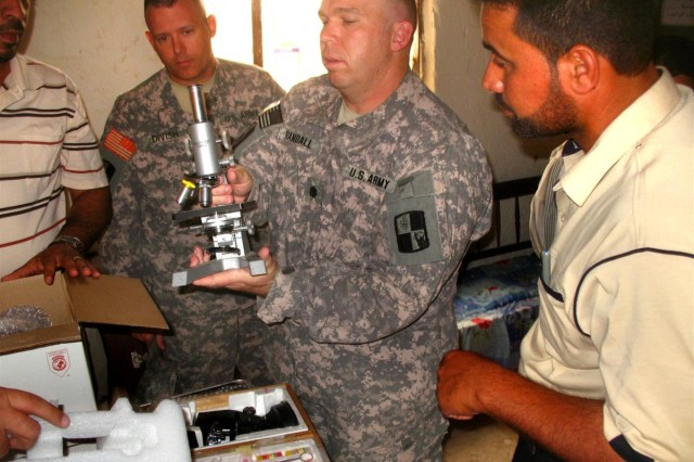 Lt. Col. Tony Divish, 287th Special Troops Battalion commander, and Lt. Col. Anthony Randall, 287th STB executive officer, explains the features of a professional microscope to the teachers of Al Moamen School, in Dhi Qar Province, Iraq May 5. The unit recently adopted the school and presented two microscope sets in addition to school supplies to the teachers and students.