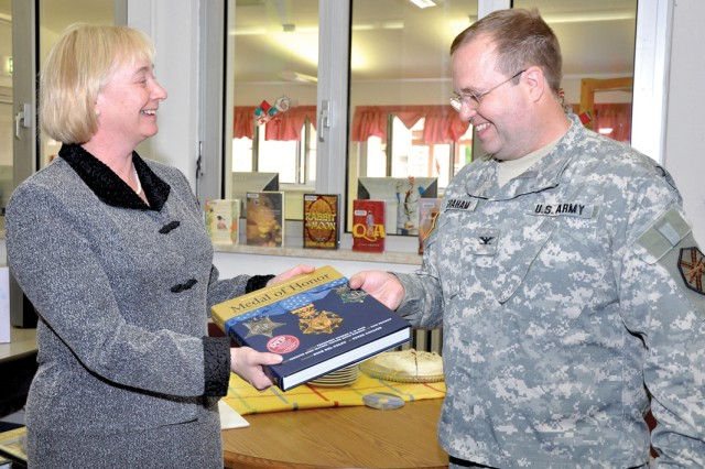 "Christine Havlik presents Col. Ray Graham with a ""Medal of Honor -- Portraits of Valor Beyond the Call of Duty"" book on behalf of George Patton Waters."