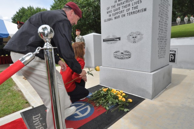 Family members of a fallen Paratrooper from the 82nd Airborne Division place a yellow rose at the base of the Global War on Terrorism memorial during the All American Memorial Ceremony at the 82nd Airborne History Museum, May 18. The memorial ceremony is held every year during the 82nd's All American Week Celebration to honor the sacrifices of past and present Paratroopers and their families.  (U.S. Army photo by Sgt. Susan Wilt, 2nd BCT, 82nd Abn. Div. PAO)