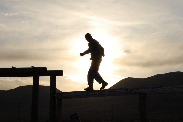 A Pre-Ranger student is silhouetted against the sun as he carefully balances his way across a log on the obstacle course portion of the Pre-Ranger Course, May 18. (Photo by Spc. Nathaniel Muth, 11th ACR Public Affairs)
