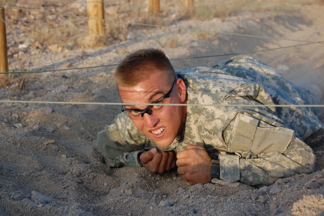 Spc. Daniel Worthington, a Pre-Ranger student, high-crawls through the dirt during the obstacle course portion of the Pre-Ranger Course, May 18.