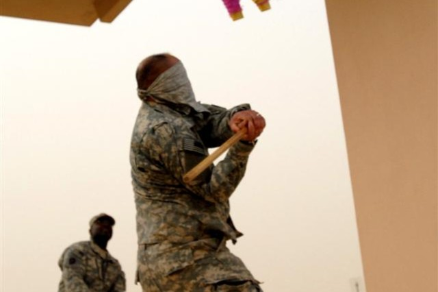 Sgt. 1st Class Jose M. Orozco, from Hillsborough, Texas, takes a swing at a piñata during a Cinco de Mayo celebration at Al Asad Air Base, Iraq May 5. Every month, the Soldiers of 2nd Battalion, 142nd Infantry Regiment celebrate a different cultural holiday.