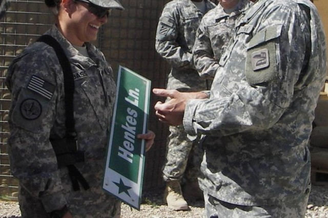 Capt. Linda A. Bass, a support operations resource plans officer for the 3d Sustainment Command (Expeditionary), receives a road sign named in honor of her brother by Lt. Col. Jeffrey M. Sabatine, Marez garrison commander at Forward Operating Base Marez, Iraq, March 31.