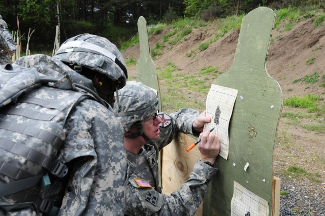 A group of 13 Noncommissioned Officers and Soldiers from U.S. Army garrisons across Europe gathered at USAG Grafenwoehr to compete for the titles of Soldier of the Year and NCO of the Year for Installation Management Command-Europe, May 10-13, 2009. NCO of the Year competitor Staff Sgt. Daniel Gaumer triangulates his shot pattern with his sponsor while zeroing his weapon at the range.