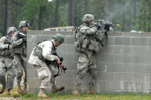 Soldiers assigned to Company C, 2nd Battalion, 69th Armor Regiment, 3rd Heavy Brigade Combat Team, 3rd Infantry Division, react to enemy fire during a training exercise at the Selby Military Operations Urban Terrain Site at Fort Benning, Ga., May 6. The exercise was part of Hammer Focus, the 3rd HBCT's largest field training exercise at Fort Benning.