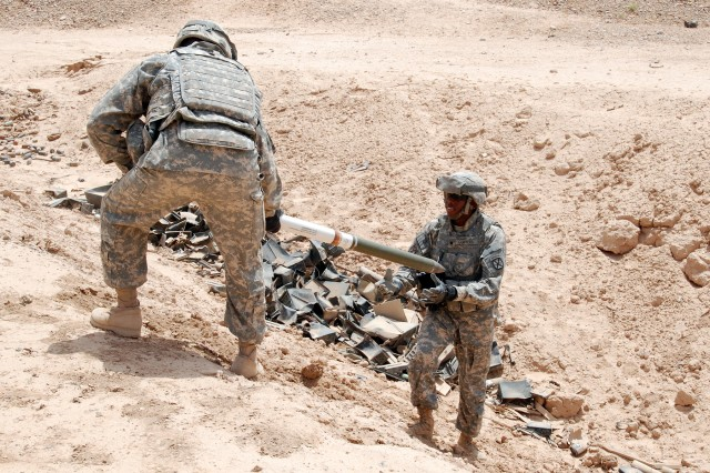 Spc. Kelvin Conyers, ammunition handler with the 277th Aviation Support Battalion, is handed an AH-12 High-Explosive rocket May 11 on Memorial Range, Contingency Operating Base, Iraq. Conyers was helping deliver a load of defective rockets to be destroyed by the Navy's Explosive Ordnance Detachment.