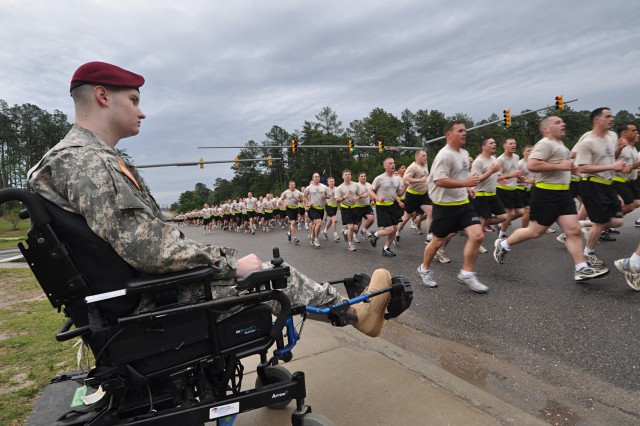 Philippi, W. Va. native, Sgt. John Hoxie, Co. C, 1st Battalion 325th Airborne Infantry Regiment, 2nd Brigade Combat Team, 82nd Airborne Division, watches Soldiers run by during the division run that kicked off the 82nd Airborne Division's All American Week celebration May 18. Hoxie returned to Fort Bragg for the first time since he was injured during a 2007 deployment to Iraq in order to participate in the celebration.
