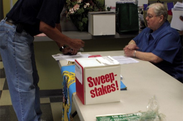 """Retired Sgt. 1st Class Juan Virella signs up for the Fort Eustis Retiree Council newsletter at the Commissary where an informational table was manned by Dorothy Baker, wife of retired Sgt. 1st Class Princes Baker, for the Fort Eustis Retiree Appreciation Day Saturday. The theme for this year's event was """"Service to the Community.""""  The annual commemoration is hosted by the retiree council. Council membership includes retired officers, warrant officers, noncommissioned officers and widows and widowers of retirees. Retirees and families in need of assistance or information may call or visit the Retirement Services Office, Bldg. 662 on Darcy Place, or call 878-3648 for assistance."""