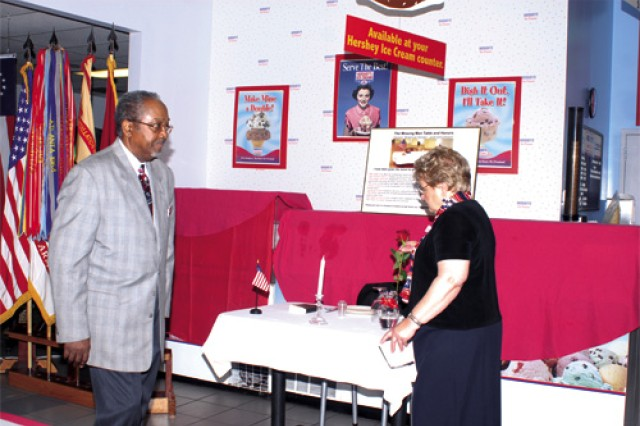 Retired Sgt. Maj. Moses Gayle Jr., Fort Eustis Retiree Council co-chair, walks by the Missing Man Table, a new part of this year's event, on his way from explaining the symbolism for the white table cloth as Peg Boarman, FERC survivor spouse advocate, makes her way to the podium to explain the significance of the single red rose. Boarman, according to retired Maj. Edward Rock Jr., FERC chair, is the only survivor spouse advocate on any retiree council in the nation.