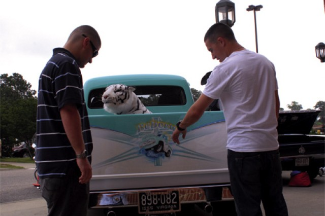 Pfc. Jared Crane, C Company, 1-222nd Aviation Regiment, points out the paint job of a 1955 Ford F-100, owned by retired Air Force Senior Master Sgt. Terry Wheeler, to Pvt. Joe Simon, C Co., 1-222nd Avn. Regt., during the Fort Eustis Retiree Appreciation Day Saturday at the Post Exchange. A 1967 Ford GTA Mustang, owned by retired Sgt. 1st Class Larry Sigme, a 1966 Corvette Stingray, owned by retired Maj. Richard Tarr, and a 1926 Buick Model 26-27, owned by Elaine Tarr, were also on display at the Antique Car and Bike Show.