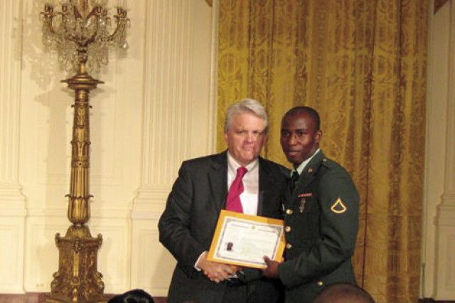 Pfc. Oswald Essel receives his Certificate of Naturalization from Mike Aytes, U.S. Citizenship and Immigration Services acting deputy director, during a ceremony May 1 at the White House.